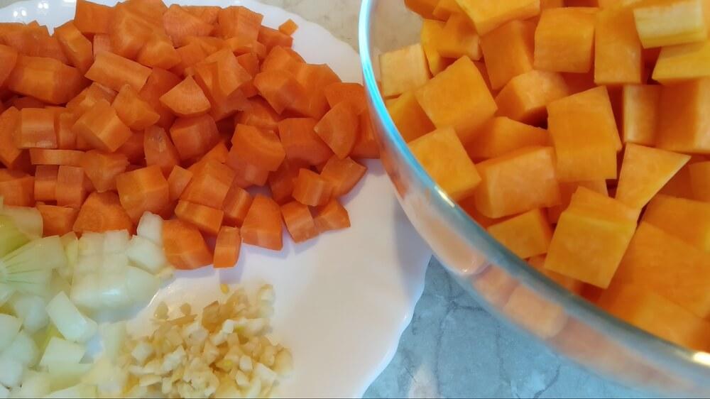 posiekana marchewka, cebula i dynia - krem z dyni